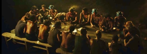 The titular coal-miners sit down for what they believe is their last meal. Image courtesy of Warner Bros.