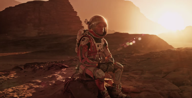 Lone Martian Mark Watney sits on a rock, contemplating his existence. Image courtesy of Twentieth Century Fox.